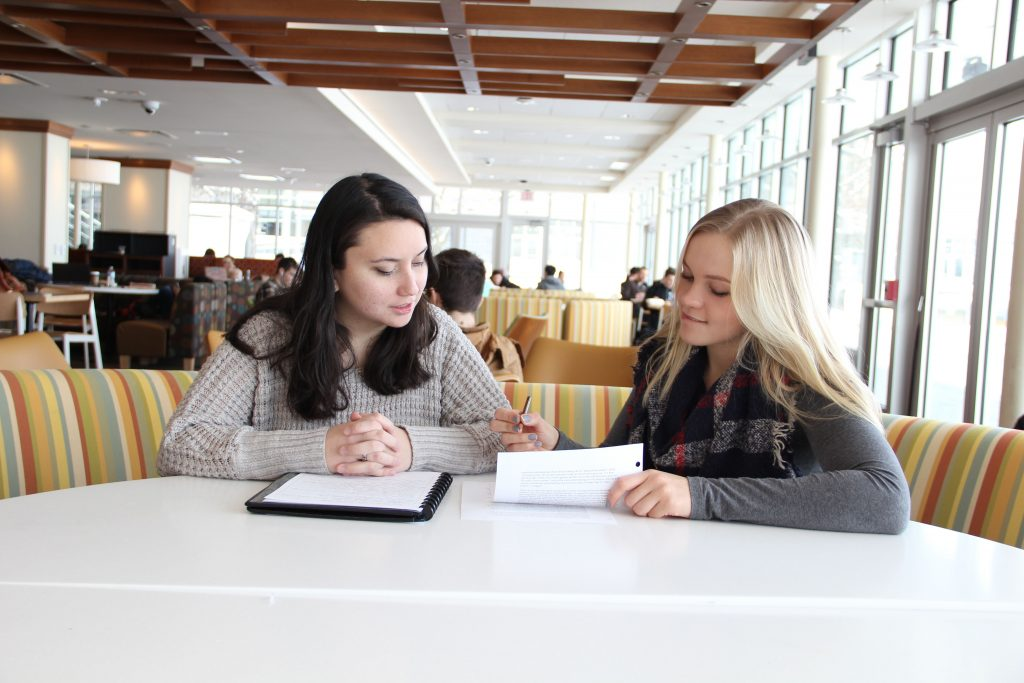 Two women sit at a table and look at a piece of writing together.